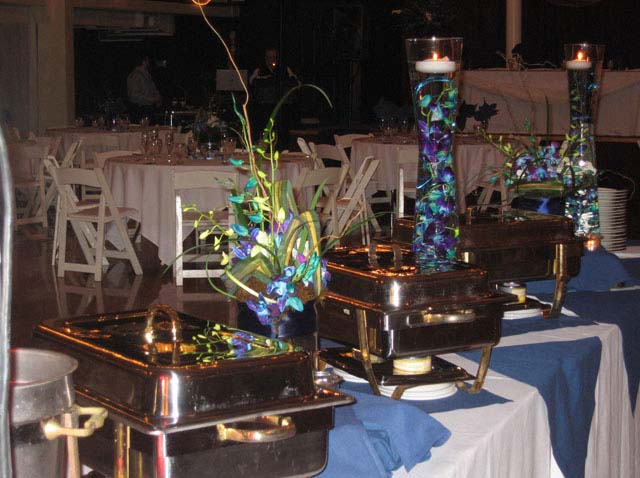 a bouquet of flowers used as a catering centerpiece set up next to a buffet station