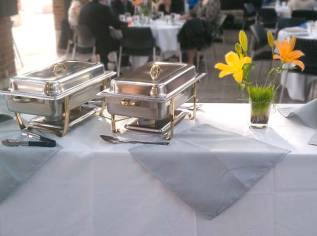 a yellow flower centerpiece next to a catering buffet station