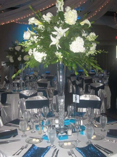 A Green Plant With White Flowers In A Glass Vase Used For A Catered Wedding  Event