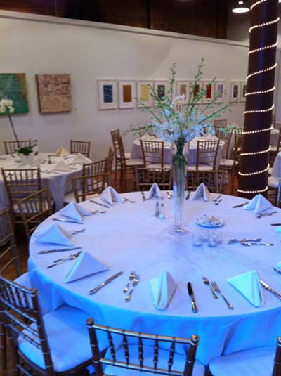 a glass centerpiece with green plants used at a wedding