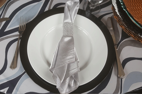 catering plates and silverware wrapped in a silver napkin
