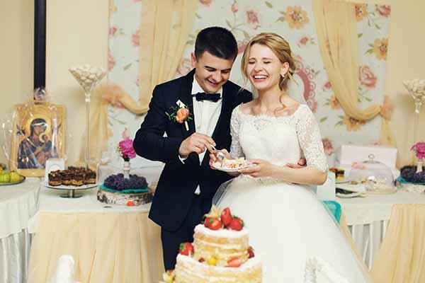 Happy wedding couple handsome groom and blonde bride eating deli