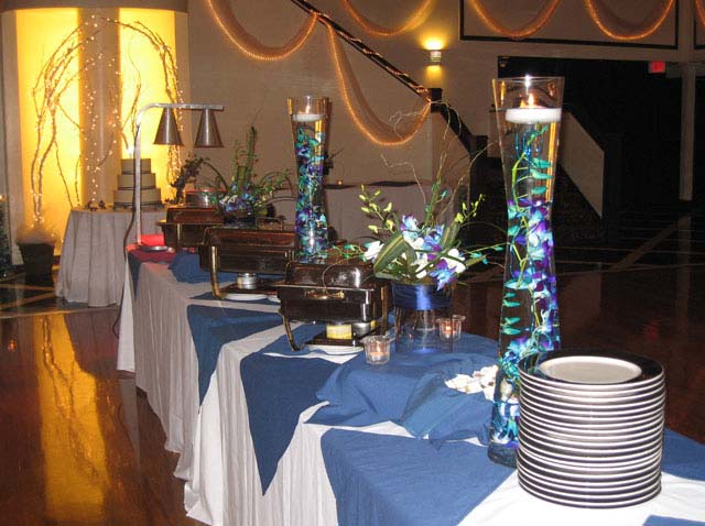 a glass centerpiece with blue and green marbles set up near a catering buffet station