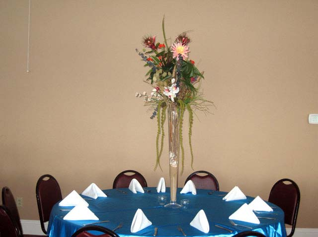 a bouquet of flowers on top of a blue table cloth with white napkins used for catering