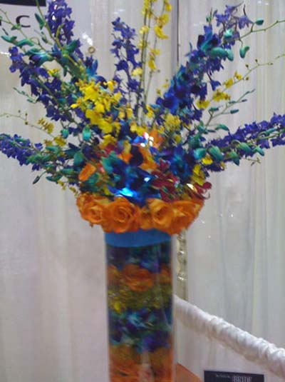 a blue and yellow floral arrangement in a matching vase with orange trim used at a catering event