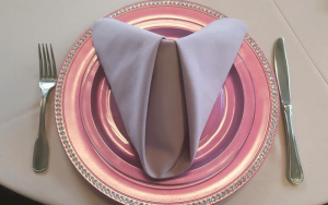 a pink metallic plate and lavender napkin for catering