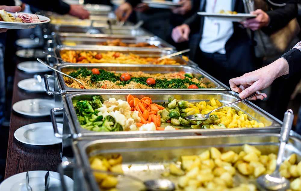 People serving themselves at a catered buffet